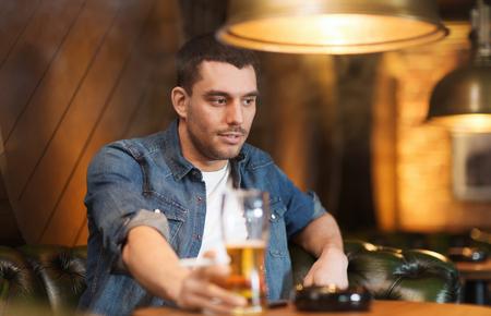 malos habitos: las personas y los malos hábitos concepto - joven hombre de cerveza beber y fumar cigarrillos en el bar o pub
