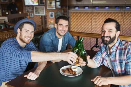 bachelor: people, leisure, celebration, friendship and bachelor party concept - happy male friends drinking beer and clinking bottles at bar or pub