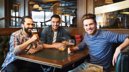 party table: people, leisure, friendship and and bachelor party concept - happy male friends drinking beer at bar or pub