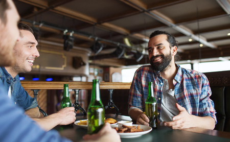 bachelor: people, leisure, friendship and bachelor party concept - happy male friends drinking bottled beer and talking at bar or pub