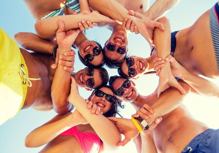 hands connected: friendship, summer vacation, teamwork and people concept - group of smiling friends wearing swimwear standing in circle over blue sky holding hands connected to each other