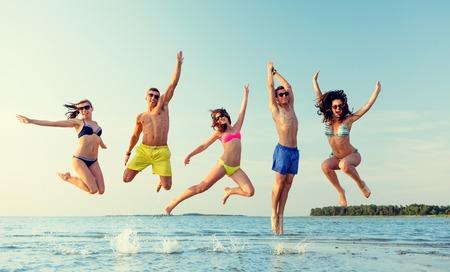 traje de baño: amistad, el mar, las vacaciones de verano, las vacaciones y la gente concepto - grupo de amigos sonriendo vistiendo trajes de baño y gafas de sol salta en la playa Foto de archivo