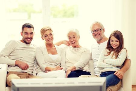 Familie, Glück, Generation und Menschen Konzept - glückliche Familie sitzt auf dem Sofa und Fernsehen zu Hause