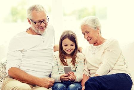 grandfather: familia, generaci�n, la tecnolog�a y el concepto de la gente - abuelo sonriente, nieta y abuela con smartphone sentado en el sof� en casa Foto de archivo