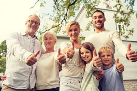 family, happiness, generation, home and people concept - happy family standing in front of house and showing thumbs up outdoors Imagens