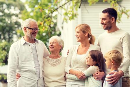 casita de dulces: familia, la felicidad, la generación, el hogar y las personas concepto - la familia feliz que se coloca delante de la casa al aire libre Foto de archivo