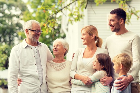 three generations of women: family, happiness, generation, home and people concept - happy family standing in front of house outdoors Stock Photo
