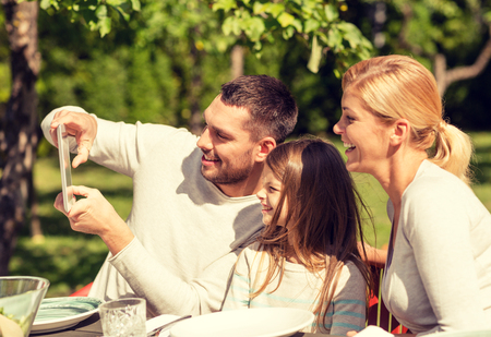 computer generation: family, happiness, generation, home and people concept - happy family sitting at table and taking selfie with tablet pc computer outdoors