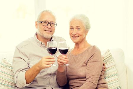 tomando vino: familia, días de fiesta, las bebidas, la edad y las personas concepto - feliz pareja senior con vasos de vino tinto en casa