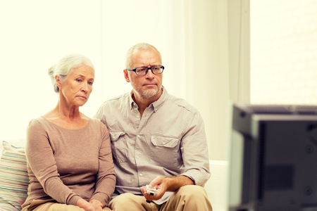 people watching: family, technology, age and people concept - senior couple watching tv at home Stock Photo