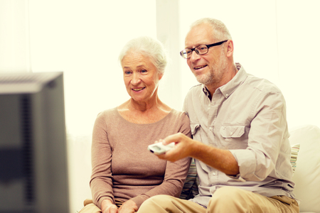 pareja viendo television: family, technology, age and people concept - happy senior couple watching tv at home