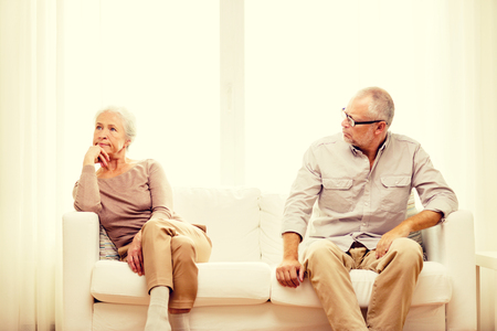 family sofa: family, relations, age and people concept - senior couple sitting on sofa at home