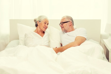 bedtime: family, bedtime, resting, age and people concept - happy senior coupler lying in bad at home Stock Photo