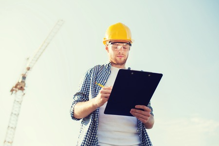 paperwork: business, building, paperwork and people concept - builder in hardhat with clipboard outdoors