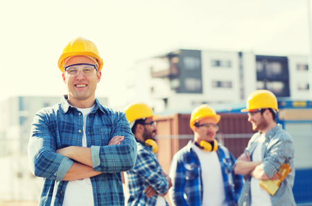 co work: business, building, teamwork and people concept - group of smiling builders in hardhats outdoors