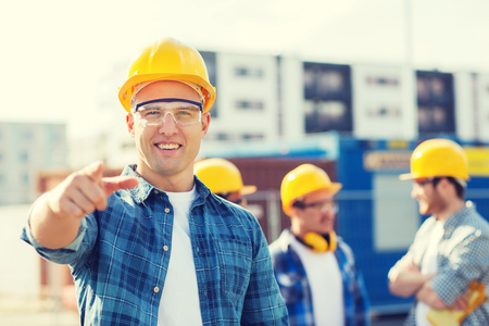 business, building, teamwork, gesture and people concept - group of smiling builders in hardhats pointing finger on you outdoors