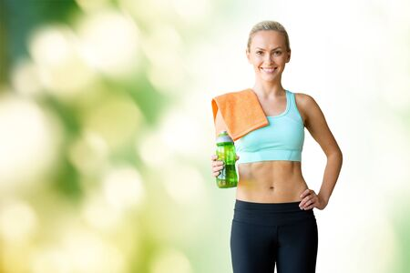 warm up: fitness, sport, training, drink and lifestyle concept - woman with bottle of water and towel over green natural background