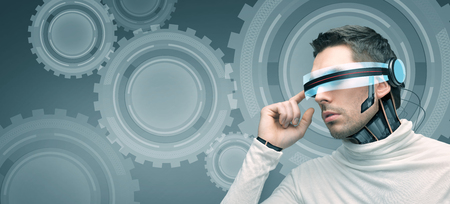 people, technology, future, engineering and progress - man with futuristic 3d glasses and microchip implant or sensors over blue background with cogwheel mechanism projection Stock Photo