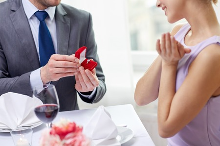 couple, love, engagement and holiday concept - close up of excited young woman and boyfriend giving her ring at restaurant Stockfoto