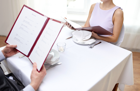 person reading: restaurant, food, eating and holiday concept - close up of couple with menu choosing dishes at restaurant Stock Photo