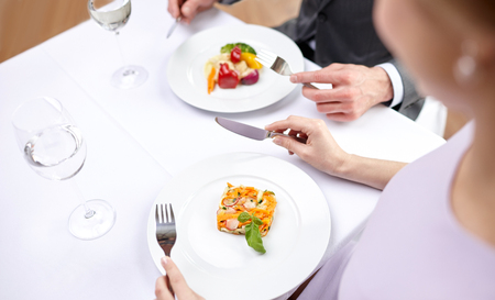 two on top: restaurant, food, people, date and holiday concept - close up of couple eating appetizers at restaurant Stock Photo