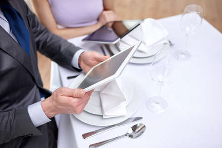 people on computers: technology, people, food and holiday concept - close up of couple with menus on tablet pc computers at restaurant