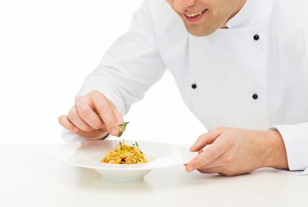 plato de comida: cocinar, profesión, alta cocina, la comida y la gente concepto - cerca de cocinero de sexo masculino feliz cocinar decorar el plato Foto de archivo