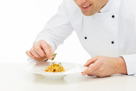 food dish: cooking, profession, haute cuisine, food and people concept - close up of happy male chef cook decorating dish Stock Photo