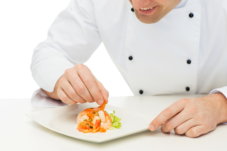 chef kitchen: cooking, profession, haute cuisine, food and people concept - close up of happy male chef cook decorating dish Stock Photo