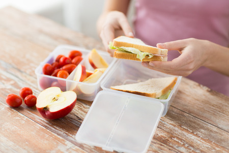 food storage: healthy eating, storage, dieting and people concept - close up of woman with food in plastic container at home kitchen