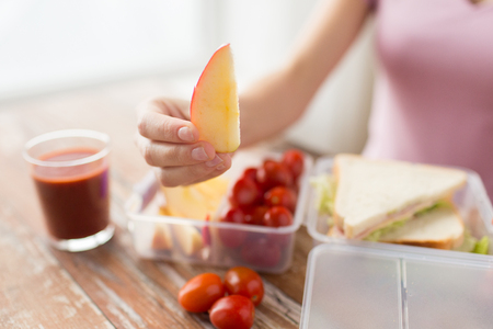 lunch table: healthy eating, storage, dieting and people concept - close up of woman with food in plastic container at home kitchen