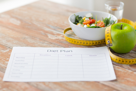 meals: healthy eating, dieting, slimming and weigh loss concept - close up of diet plan paper green apple, measuring tape and salad Stock Photo