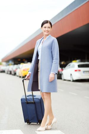 viajes, viaje de negocios, la gente y el concepto de turismo - mujer joven con bolsa de viaje sobre taxis sonriendo a la terminal del aeropuerto o estación de tren