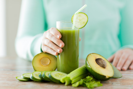 natural juices: healthy eating, food, dieting and people concept - close up of woman hands with green fresh juice and vegetables sitting at table
