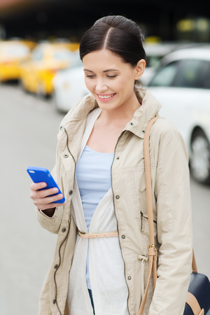 trip over: travel, business trip, people and tourism concept - smiling young woman with smartphone over taxi station or city street