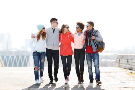 personas unidas: el turismo, los viajes, la gente y el concepto de la amistad - grupo de amigos adolescentes felices que recorren a lo largo de calle de la ciudad y que hablan Foto de archivo