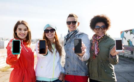 le persone, l'amicizia, il cloud computing, la pubblicità e il concetto di tecnologia - gruppo di amici sorridenti adolescente mostrando schermi di smartphone vuote all'aperto