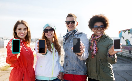 people, friendship, cloud computing, advertising and technology concept - group of smiling teenage friends showing blank smartphone screens outdoors