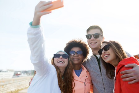pretty black woman: people, leisure, friendship and technology concept - group of smiling teenage friends taking selfie with smartphone outdoors