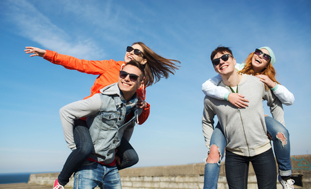 fashion boy: friendship, leisure and people concept - group of happy teenage friends in sunglasses having fun outdoors