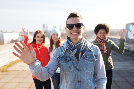 waving: people, friendship and international concept - happy african american young man or teenage boy in front of his friends waving hands on city street