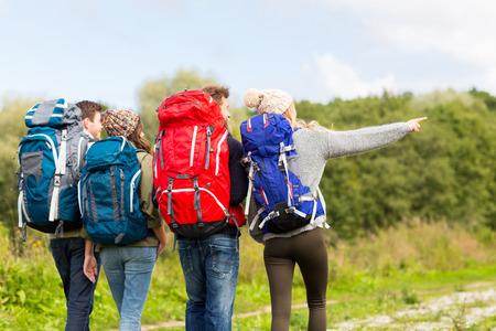 Aventure, Voyage, tourisme, randonnée pédestre et les gens concept - groupe d'amis marchant avec des sacs à dos de l'arrière Banque d'images - 54330988