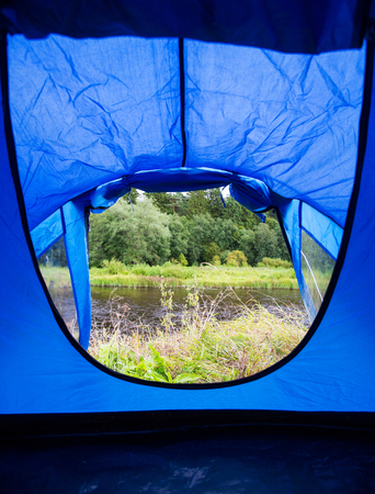 undeveloped: camping, travel, tourism, hike and people concept - view from blue tourist tent entrance to lake or river landscape