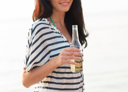 nonalcoholic beer: summer vacation, holidays, drinks and people concept - close up of smiling young woman drinking from bottle on beach