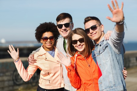 happy black woman: friendship, tourism, travel and people concept - group of happy teenage friends in sunglasses hugging and waving hands outdoors