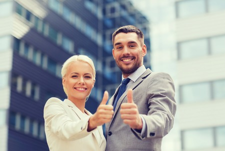 business partnership: business, partnership, success, gesture and people concept - smiling businessman and businesswoman showing thumbs up over office building Stock Photo