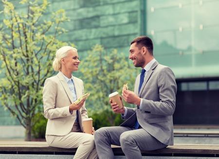 Unternehmen, Partnerschaft, Essen, Getränke und die Menschen Konzept - lächelnd Geschäftsleute mit Pappbecher stehend über Bürogebäude