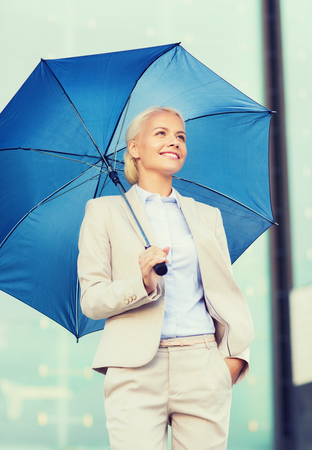 executive woman: business, bad weather and people and concept - young smiling businesswoman with umbrella outdoors