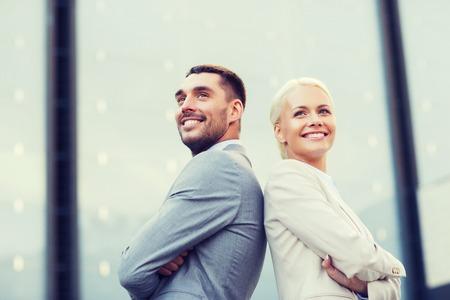 ビジネスマンやビジネスウーマンの事務所ビルの上に立って笑顔 - ビジネス、パートナーシップ、成功および人々 の概念