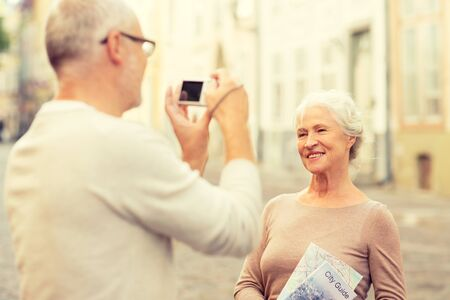 family together: age, tourism, travel, technology and people concept - senior couple with map and camera photographing on street